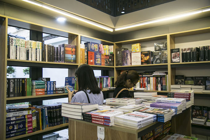 A student chats on her phone while browsing the dictionary section at a book store in Hanois Book Street. Photo by VnExpress/Bao Yen