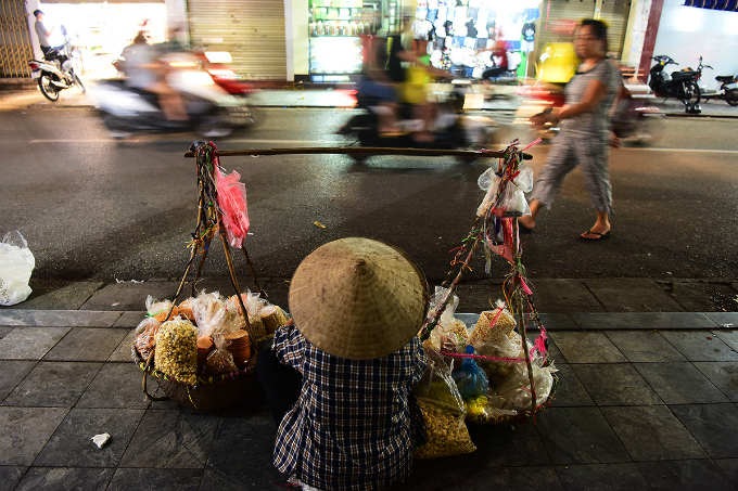 A row of goods linger on the sidewalk at 23h hoping to sell a few more food bags.