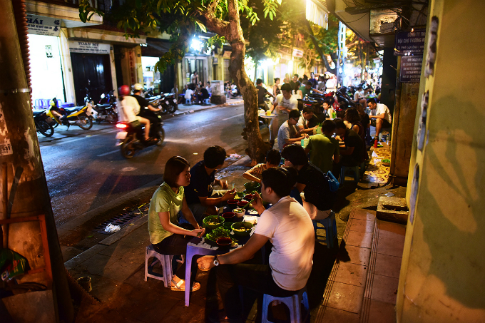 Street diners sit in long row along the sidewalk.