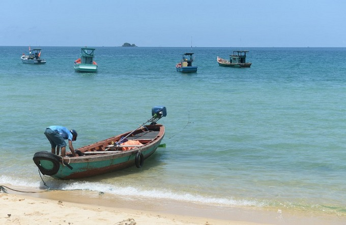 a man preparing a boat for tourists on a beach in Phu Quoc Island in southern Vietnam. Photo by AFP/Hoang Dinh Nam