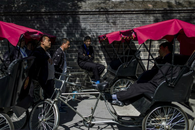 Rickshaw drivers waiting for customers in a touristic area in Beijing. Photo by AFP/Fred Dufour