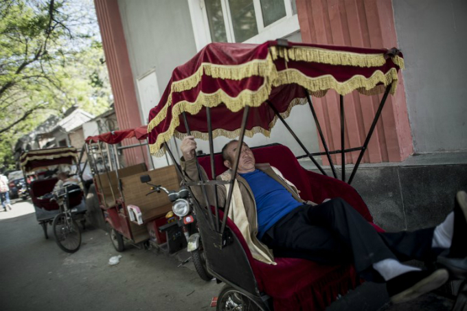 A rickshaw driver taking a rest in Beijing. Photo by AFP/Fred Dufour