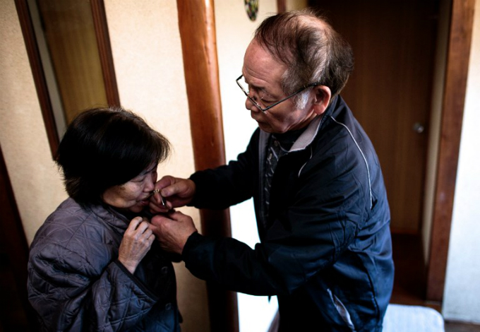 Kanemasa Ito (R) puts an identity bracelet on his dementia-stricken wife Kimiko before taking her out for a walk in Kawasaki. Photo by AFP/Behrouz Mehri