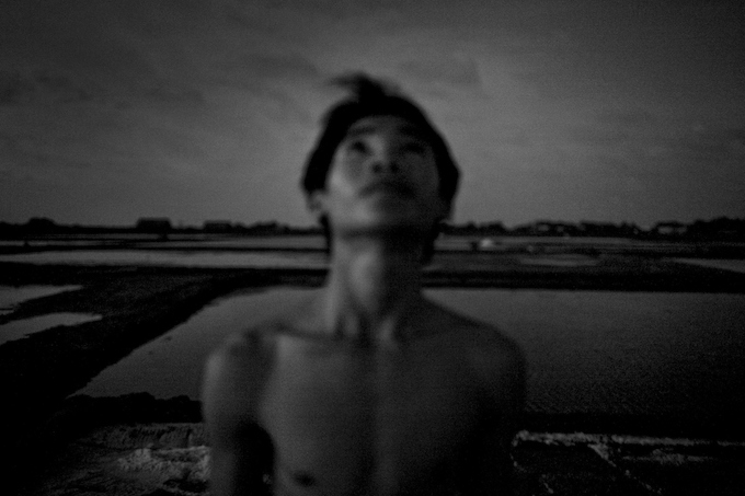 Phong Quyen, 16, takes a break from scraping salt and stares up at the night sky. Farmers harvest salt cultivated in rice-patty like fields in Ben Tre.