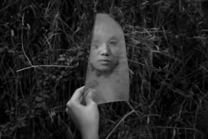 Ngan Nguyen is reflected in a mirror fragment that she found in an abandoned lot in Ho Chi Minh City.