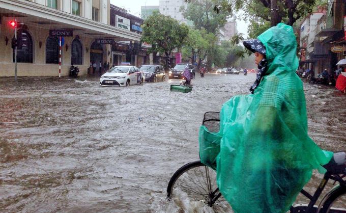 The center also forecasts that from now until June 15, Hanoi and the northern region will continue to experience heavy rains while low-lying areas will be prone to flooding and mountainous areas may be subject to flash floods and landslides. In photo: Hang Bai Street in Hoan Kiem District turns into a river as people and vehicles wades through the flood.