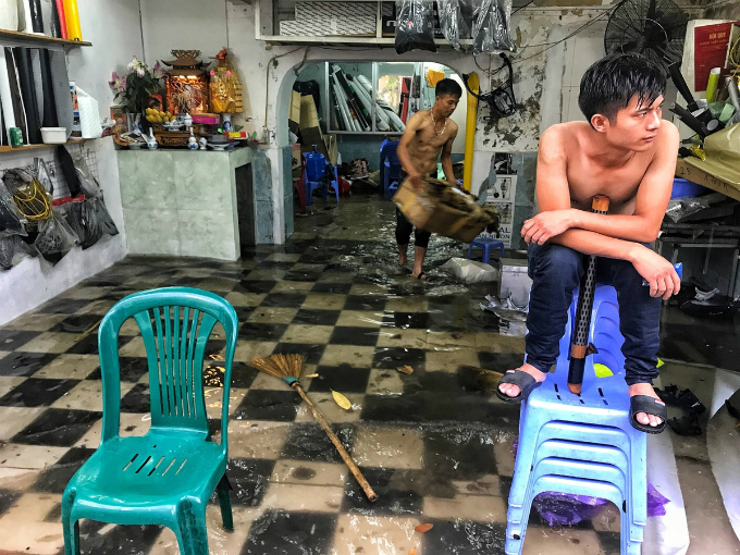 The flooding enters a nylon store on Cao Ba Quat Street, leaving the staff little to do but wait.