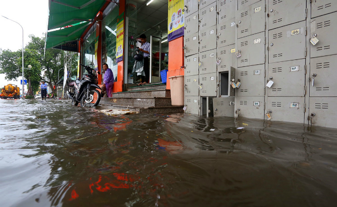 The rain lasts until 9:30a.m. but the water does not recede immediately. A supermarket on Le Trong Tan Street is flooded under 60cm deep of water.