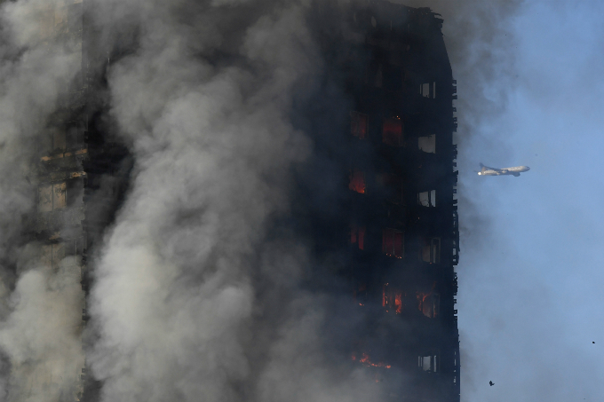 An airplane is seen as flames and smoke billow as firefighters deal with a serious fire in a tower block at Latimer Road in West London, Britain June 14, 2017. Photo by Reuters/Toby Melville