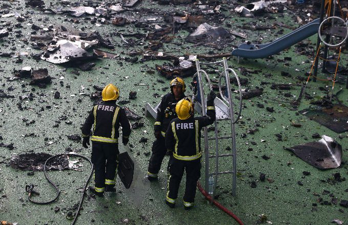 Firefighters stand amid debris in a childrens playground near a tower block severly damaged by a serious fire, in north Kensington, West London, Britain June 14, 2017. Photo by Reuters/Neil Hall