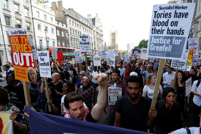 Demonstrators hold up banners during a march in Westminster, following the fire that destroyed The Grenfell Tower block, in north Kensington, West London, Britain June 16, 2017. Photo by Reuters/Peter Nicholls