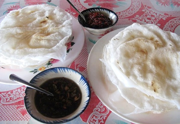 A serving of girdle cake includes steamed thin rice pancake sandwiched between two grilled ones. To enjoy the dish, you should use your hands to slightly flap them down so that they are crumbled. Later, you roll the dish and dip it into fish sauce paste, which is a mixture of fish sauce, sugar, caramelized onions, chopped pine apple, garlic, and green horn pepper. The most famous girdle cake is served at Madam Gia restaurant in Cam Nam ward. Photo credit: Thien Nguyen.