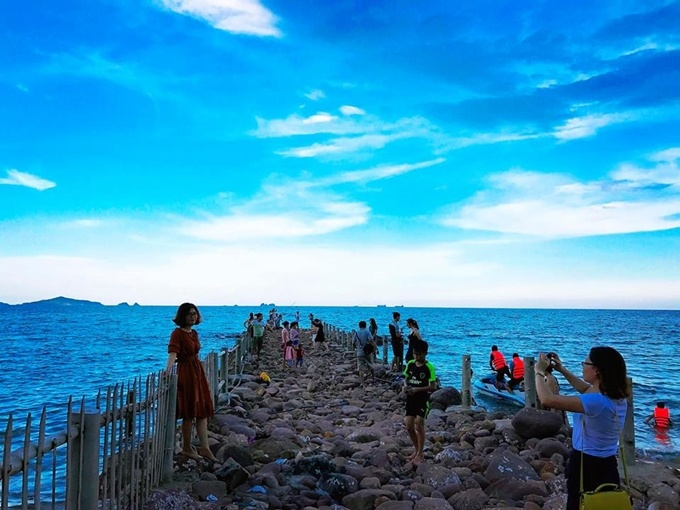 Visitors enjoy swimming in the sea, wandering along the beach, taking photos along the reefs.