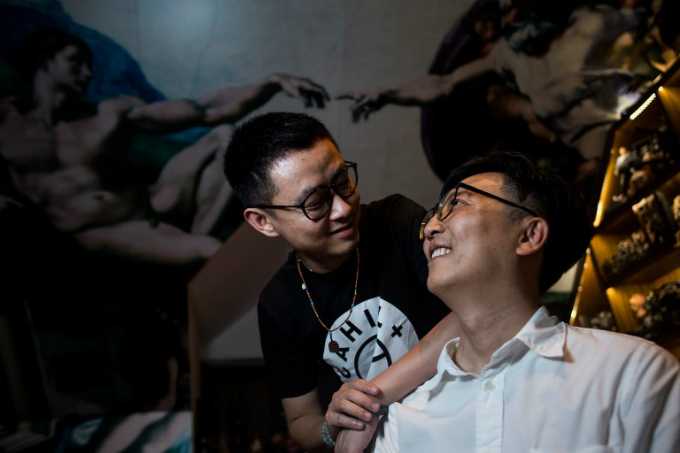 Duan Rongfeng (L) and Li Tao posing for a picture in their apartment in Shanghai. Photo by AFP/
