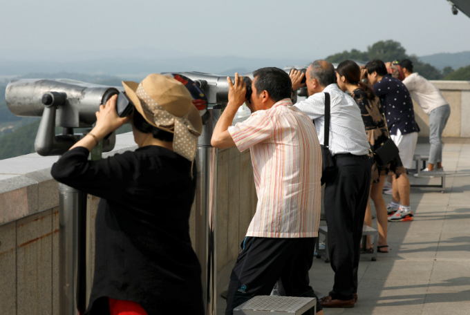 People look toward a North Korean village through a pair of binoculars at an observation post near the demilitarized zone separating the two Koreas in Paju, South Korea, July 19, 2017. Picture taken on July 19, 2017. REUTERS/Kim Hong-Ji