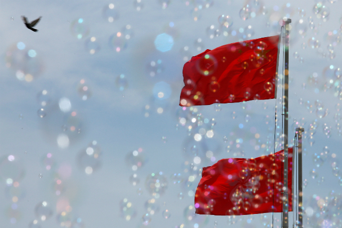 Bubbles are seen in front of a Chinese national flag (top) and a Hong Kong flag, during a Bubble Up show by Japanese artist Shinji Ohmaki, outside Harbor City mall in Hong Kong, China August 2, 2017. Photo by Reuters/Bobby Yip