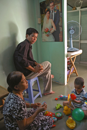 Nguyen Anh Tuan (Dylan) plays on the floor of his grandmothers house in Ho Chi Minh City in 2012. In the background hangs a picture of his mother Nguyen Do Thi Thu Giang who died giving birth to him. His American father, Christopher J. Smith, refused to help the child achieve his birthright citizenship until a Florida attorney compelled him to submit to a DNA paternity test and fill out the paperwork necessary to grant the child a passport.