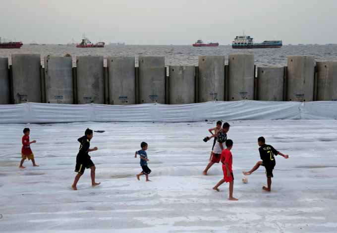 Children play soccer near a new construction of a concrete sea wall at Cilincing area in Jakarta, Indonesia August 22, 2017. Photo by Reuters/Beawiharta