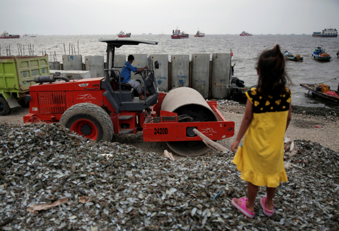A child stand as a worker drives heavy equipment near a new construction of a concrete sea wall at Cilincing area in Jakarta, Indonesia August 22, 2017. Picture taken August 22, 2017. Photo by Reuters/Beawiharta