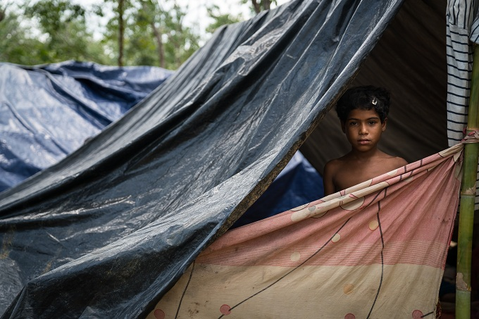 A young Rohingya girl inside her tent in the new Kutupalong settlement, Bangladesh on September 10, 2017. Photo by Thomson Reuters Foundation / Katie Arnold.