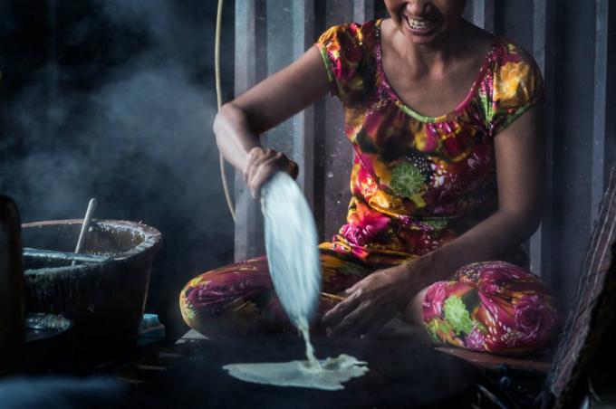 Ha Thi Sau pours a rice and sesame mixture onto a hot fire stove as she and her daughter make rice paper at their home in Thuan Hung Village in the Mekong Delta. Photo by AFP/Roberto Schmidt