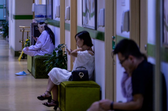 a young woman (L) with a bandaged face sits inside Huamei Medical Cosmetology Hospital in Shanghai. Photo by AFP/Chandan Khanna