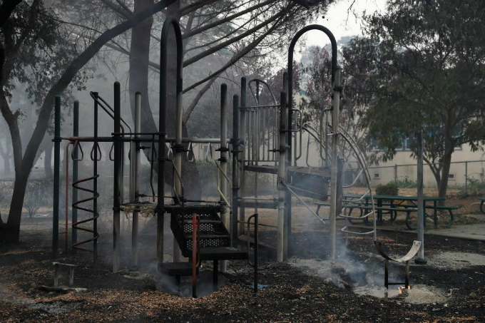 Smoke rises from a playground in front of Dunbar Elementary School during the Nuns Fire in Sonoma. Photo by Reuters/Stephen Lam