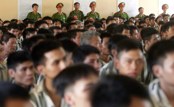 Policemen stand guard as inmates wait before being released from Hoang Tien prison, about 100km (62 miles) outside Hanoi August 30, 2013. Photo by: Reuters
