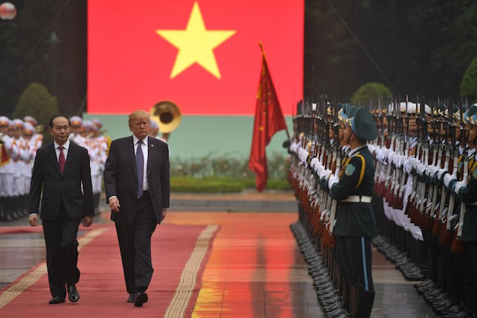 US President Donald Trump, accompanied by his Vietnamese counterpart Tran Dai Quang, inspects a guard of honour during a welcoming ceremony at the Presidential Palace in Hanoi on November 12, 2017. Photo by AFP/Jim Watson