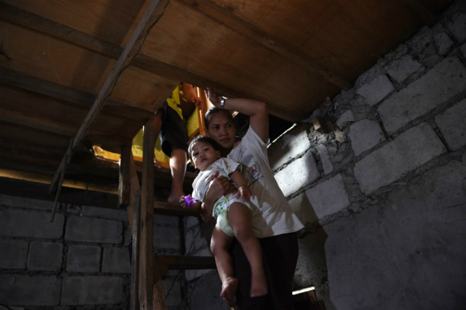 Myrna Albos, 33, carrying her child as she walks down to their house in a slum area in Manila. Photo by AFP/Ted Aljibe