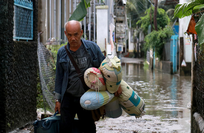 Since his rented house in Vinh Hiep Commune had been flooded, this foreign man had to pack up and move to a higher area.