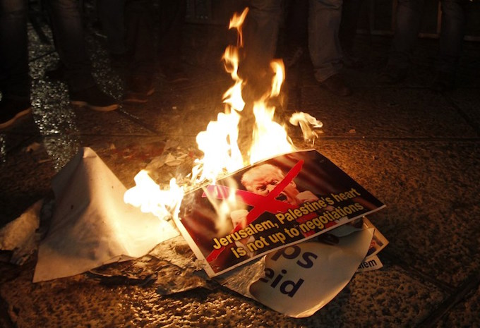 Palestinian demonstrators burn posters of the US president in Bethlehems Manger Square in protest to him declaring Jerusalem as Israels capital on December 6, 2017. Photo by AFP/Musa Al Shaer.