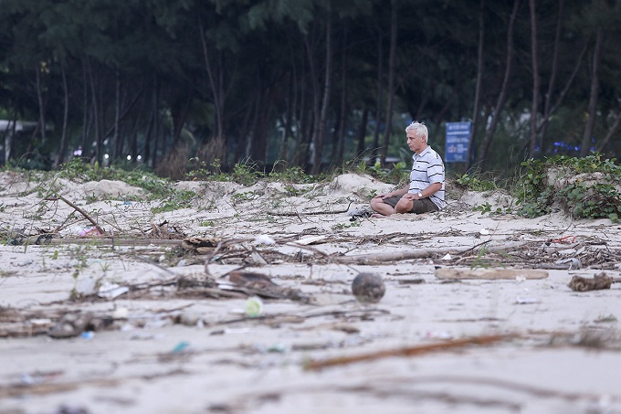 A foreign traveler meditates on the trashed shore. Da Nang Urban Environment Company said that most of the trash located on Lien Chieu District.
