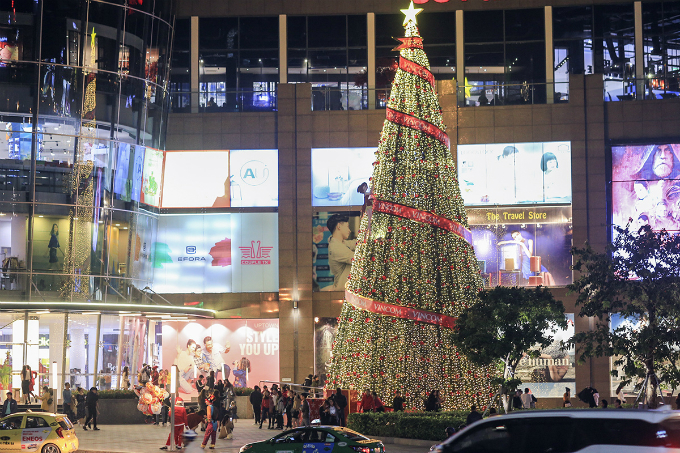 A giant Christmas tree stands outside a shopping mall.