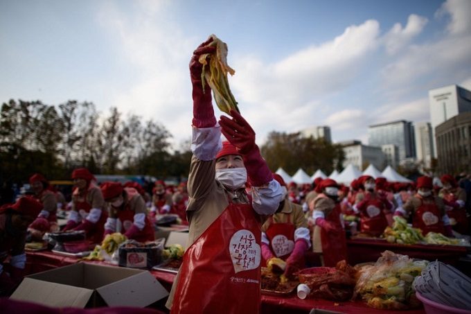 A participant holding a handful of kimchi in the air as she joins some 2000 others in a kimchi making event outside the city hall in Seoul. Photo by AFP/Ed Jones