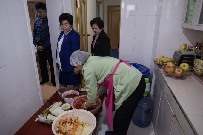Yu Yang Hui (C) makes kimchi at the apartment of Song Song-Hui (top C), in Pyongyang. Photo by AFP/Ed Jones
