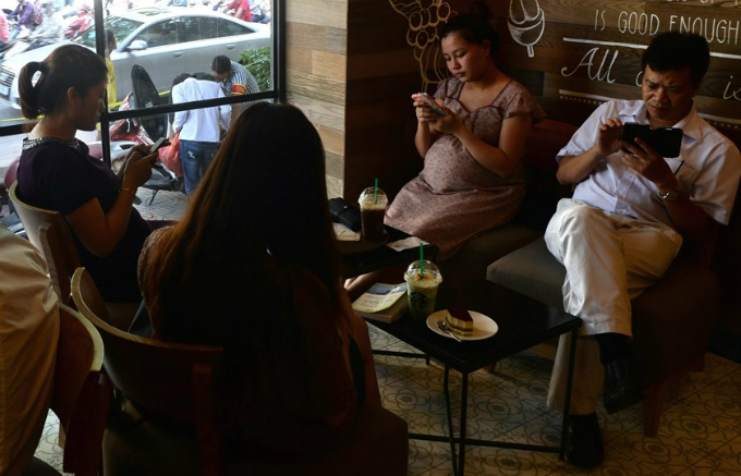 People use smartphones to check the Internet over wifi at a coffee shop in Hanoi. Photo by AFP
