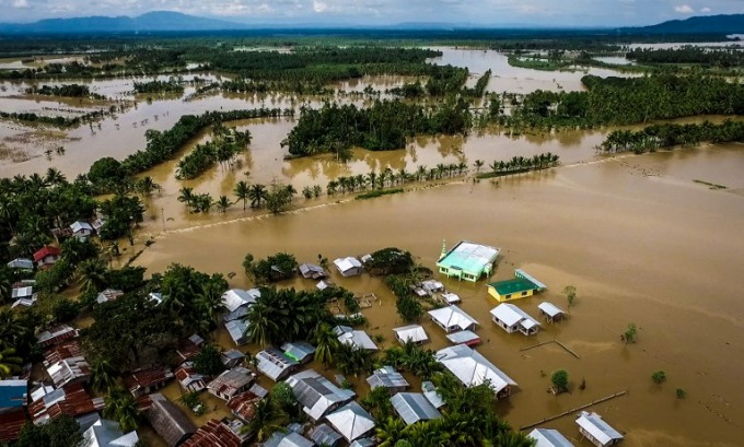 The death toll from a tropical storm in the southern Philippines climbed swiftly to 133 on December 23, as rescuers pulled dozens of bodies from a swollen river, police said. Photo by AFP/ Ferdinandh Cabrera.