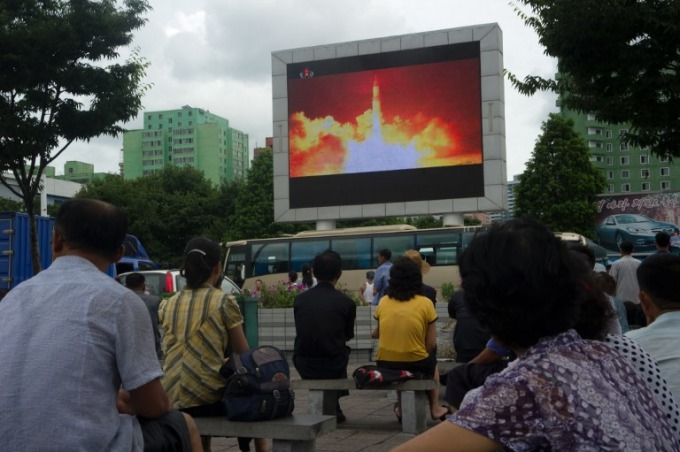 People watching as coverage of an ICBM missile test is displayed on a screen in a public square in Pyongyang. North Korea slammed fresh UN sanctions imposed over its missile tests as an act of war on December 24, 2017, its first response to the latest diplomatic move to punish Pyongyangs ever-accelerating weapons drive. Photo by AFP/Kim Won-Jin