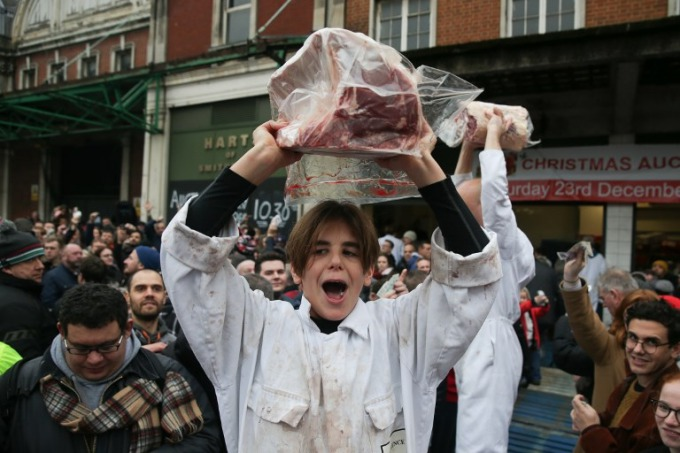A young butcher holds up cuts of meat during the traditional pre-Chrismas meat sale at Smithfield market in the city of London on December 23, 2017. Photo by AFP/Daniel Leal-Olivas