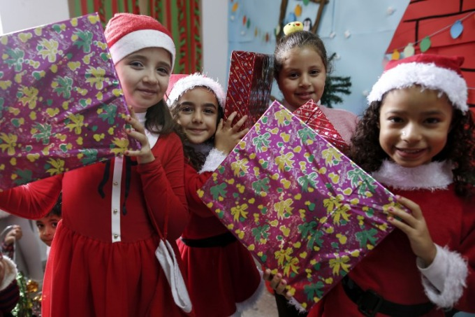Palestinian girls, some dressed in Christmas clothing, pose with wrapped boxes during a celebration at the American School in Gaza City on December 20, 2017. Photo by AFP/Mohammed Abed