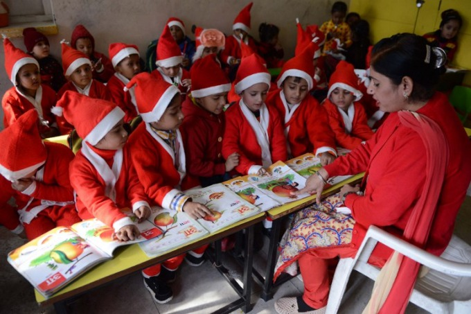 Indian schoolchildren wear Santa Claus outfits as they listen to their teacher at a school in Amritsar. Photo by AFP/Narinder Nanu.