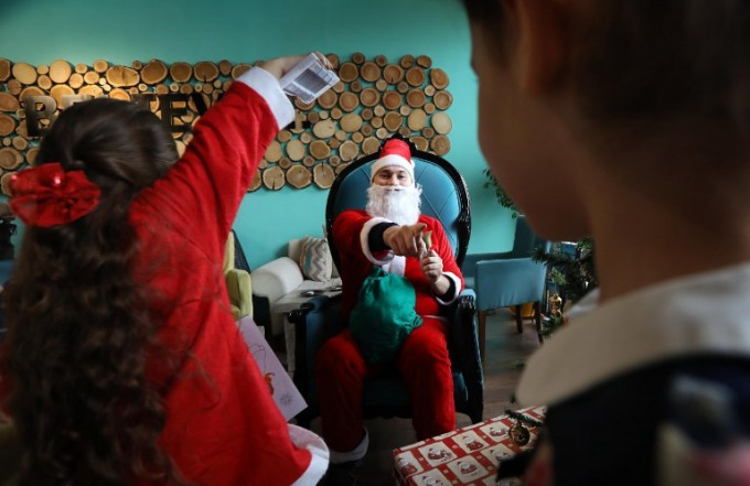 A man dressed as Santa Claus gestures as he plays with children during a Christmas event at the Book Cafe in the northern Iraqi city of Arbil, the capital of the autonomous Kurdistan region, on December 23, 2017. Photo by AFP/Safin Hamed