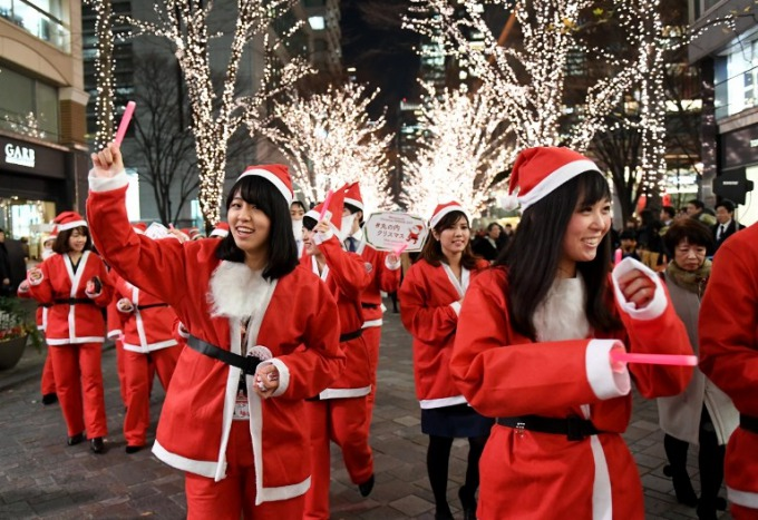 Marunouchi shop clerks and workers wearing Santa Claus costumes join a Christmas parade at the Marunouchi shopping district in Tokyo on December 22, 2017. Photo by AFP/Toshifumi Kitamura