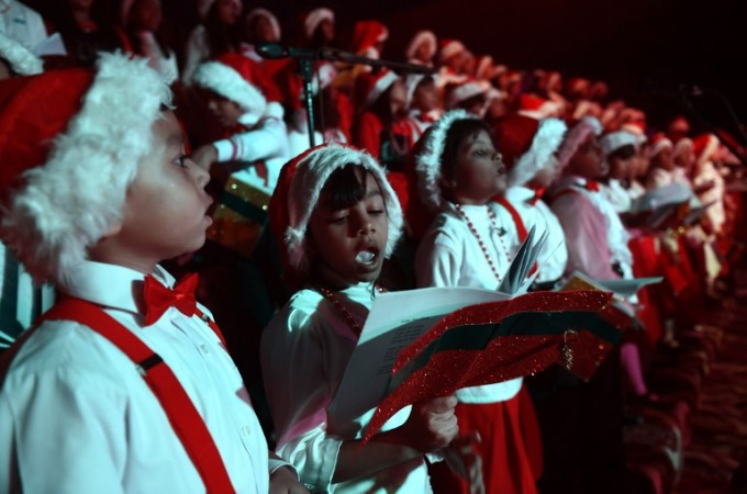 Pakistani children dressed as Santa Claus sing songs during the Christmas Carnival at the St Patrick Church in Karachi on December 22, 2017. Photo by AFP/Rizwan Tabassum