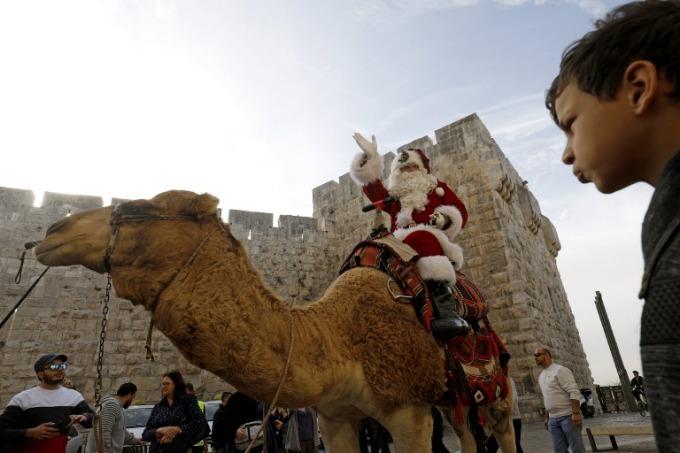 A man dressed as Santa Claus rides a camel along Jerusalems Old City Ottoman walls on December 21, 2017. Photo by AFP/Gali Tibbon
