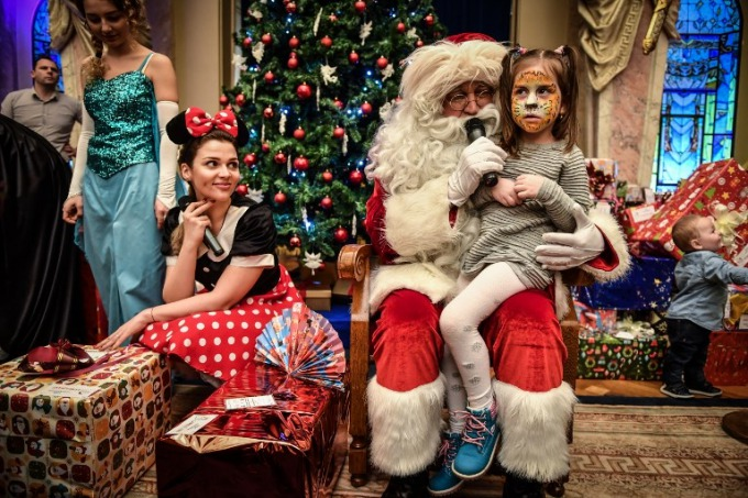 A girl waits for her present next to a man dressed as Santa Claus during a Christmas ceremony at the Palace of the National Military Club in Bucharest on December 21, 2017. Children of the Romanian Army army personnel, who were injured or died on duty, attended a childrens show and received Christmas presents. Photo by AFP/Daniel Mihalescu