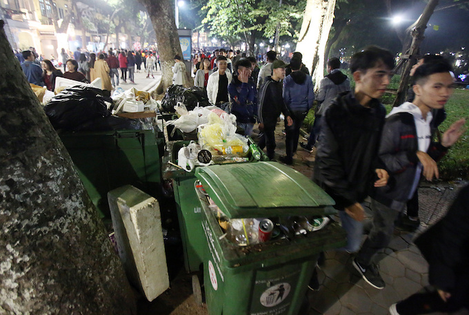 Overflowed trash bins occupy the sidewalk on Hang Khay Street.