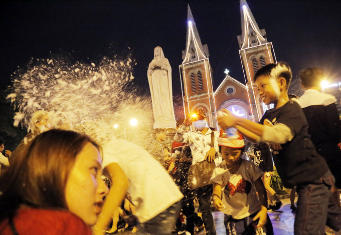 Kids play with snow spray in front of Saigons iconic Notre Dame Cathedral in District 1.