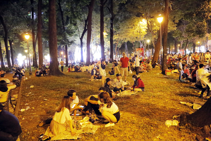 Young people sit down together for food and drink in parks across the Notre Dame Cathedral.